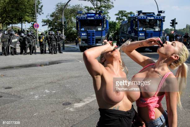 Stripper KimLaura and 'WebCam Nudist' Ginger Costello pose topless for a 'sexy protest' in front of a police unit and water cannons near Hamburg...