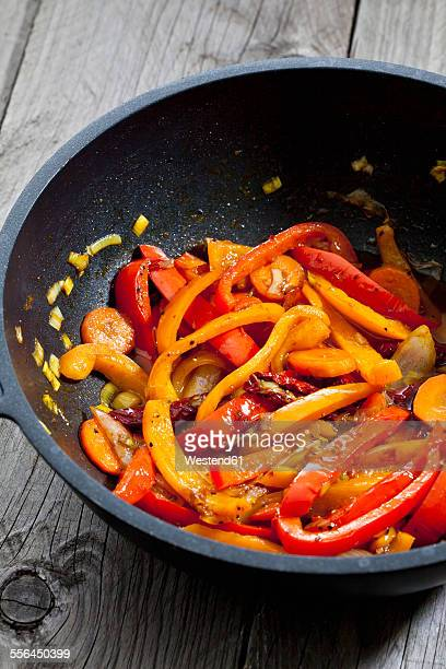 Strips of paprika, dried tomato and carrot in pan