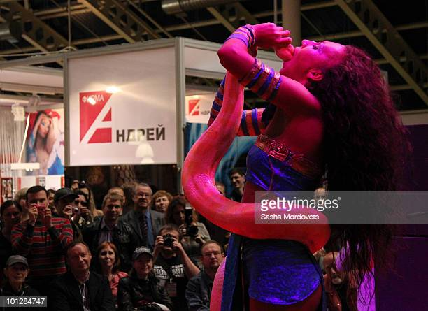 A striptease dancer performs with her snake during a show at The International Specialized XSHOW Exhibition for Adults 2010 on May 2010 in Moscow...