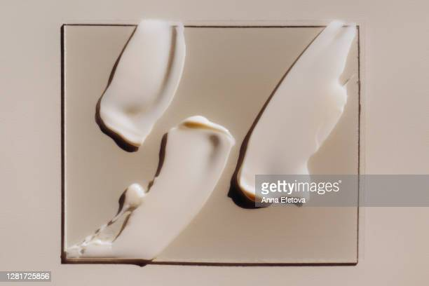 strokes of cream on piece of glass - cream coloured stock pictures, royalty-free photos & images