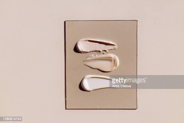 strokes of foundation cream on glass - color crema foto e immagini stock