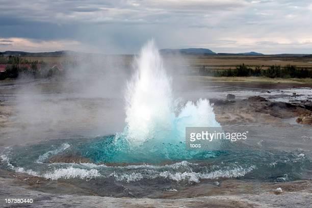 Strokkur Geyser erupts blue water with plains in background