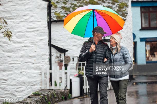 stroll through town in the rain - rain stock pictures, royalty-free photos & images