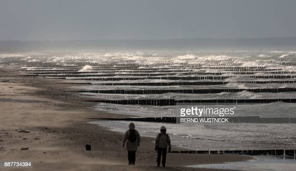 TOPSHOT Strollers are pictured in Wustrow at the Baltic Sea eastern Germany on a windy December 7 2017 PHOTO / dpa / Bernd Wüstneck / Germany OUT