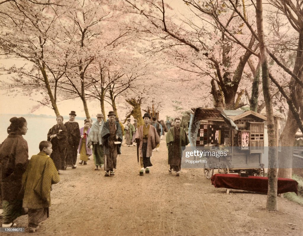 Strollers under the cherry blossoms on the bank of the Sumida River in Tokyo, circa 1890.