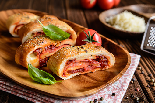 Stromboli stuffed with cheese, salami, green onion and tomato sauce 629257076