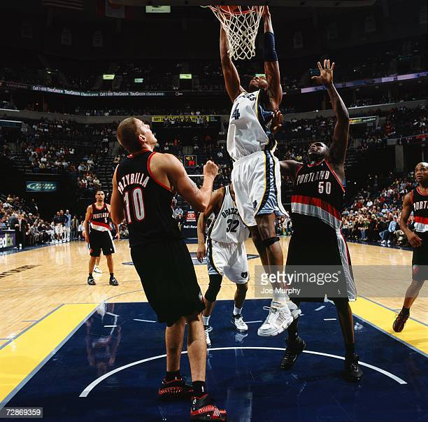 Stromile Swift of the Memphis Grizzlies takes the ball to the basket against Zach Randolph and Joel Przybilla of the Portland Trail Blazers during a...