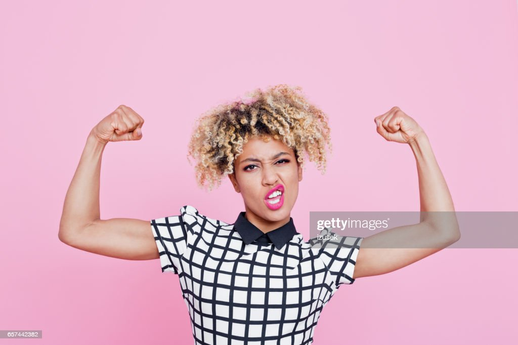 Strong afro american young woman flexing muscles : Stock Photo