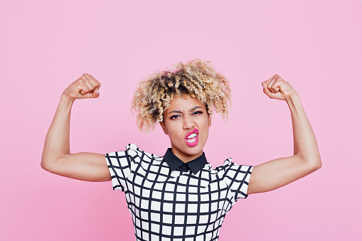 Strong afro american young woman flexing muscles 657442382