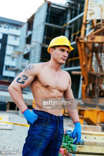 Strong and muscular manual construction worker working on construction platform