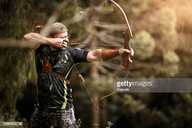 strong archer firing arrow - hunting sport stock pictures, royalty-free photos & images