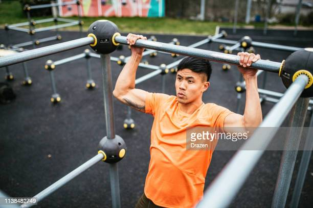 strong asian guy exercising on cloudy day, doing pull ups - sports training stock pictures, royalty-free photos & images