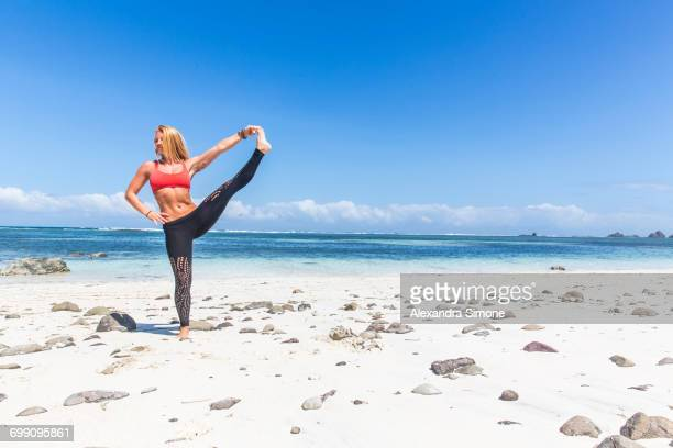 Strong athletic female in a yoga pose in Kuta, Lombok, Indonesia