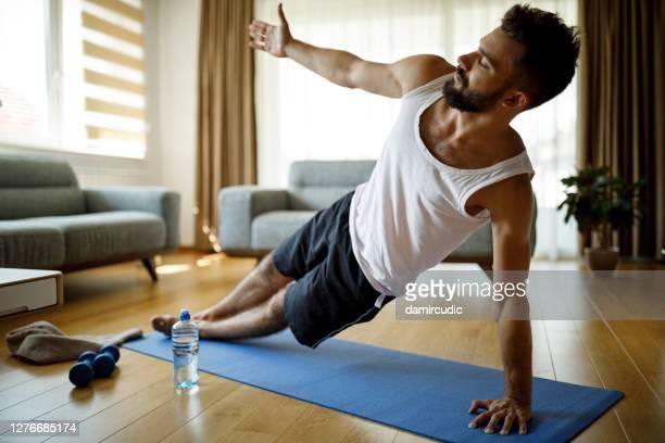 彼の家で運動強い運動若い男 - 自重トレーニング ストックフォトと画像