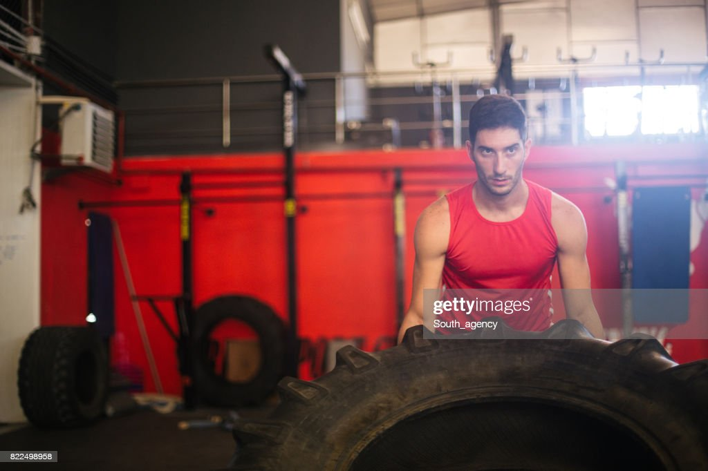 Strong Bodybuilder flipping tire at the gym : Stock Photo