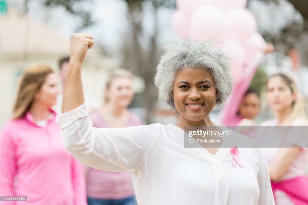 Strong breast cancer survivor flexing muscles : Stock Photo