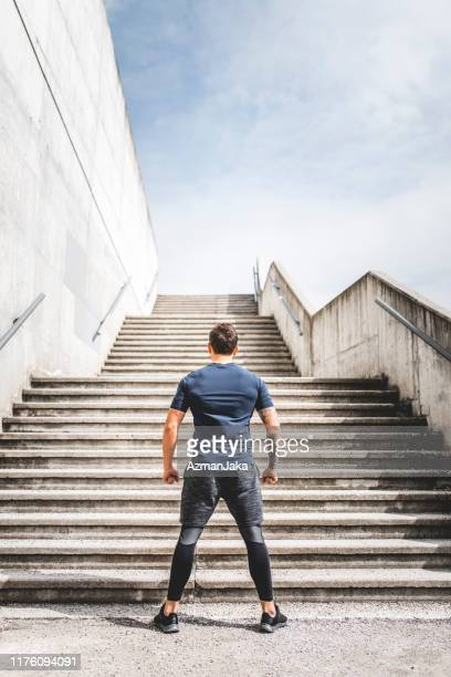 strong caucasian male athlete readying for a staircase workout - legs apart stock pictures, royalty-free photos & images