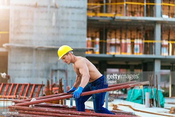 Strong construction worker carrying steel support for construction