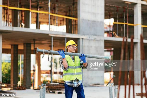 Strong construction worker working with steel support bars