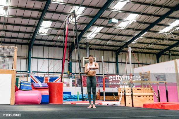 strong female gymnast checking smart watch before workout - floor gymnastics stock pictures, royalty-free photos & images