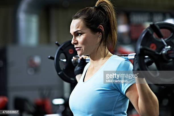 Strong Female Holding Barbell in Gym
