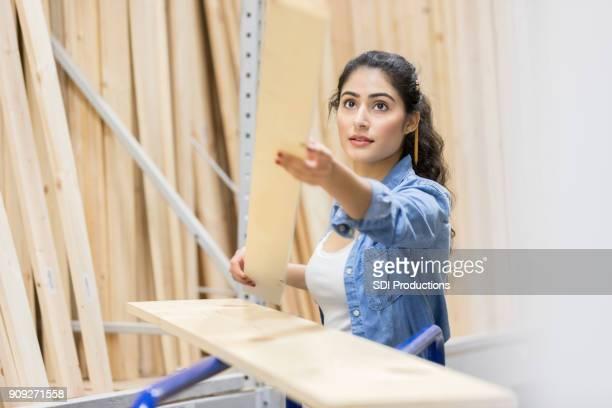 Strong female home improvement warehouse employee fills customer orders
