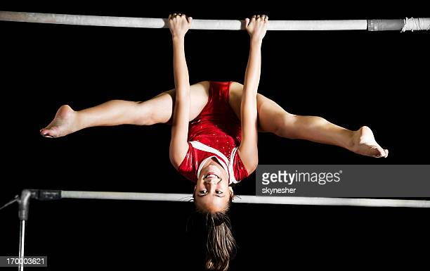 Strong gymnast girl exercising on uneven bars.
