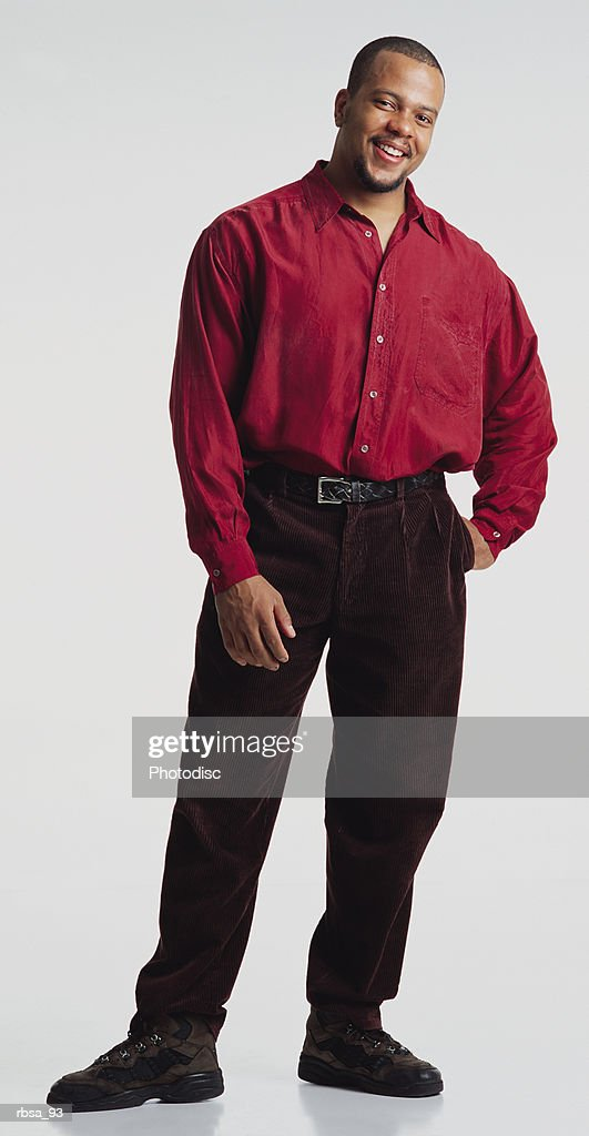 strong handsome young african american adult male in red shirt brown pants stands smiling to camera : Foto de stock