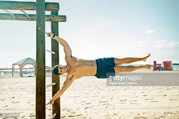 Strong healthy young man hanging from monkey bars at the beach on a summer day