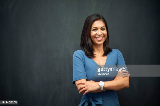 strong hispanic woman teacher - blackboard stock photos and pictures