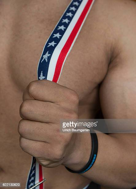 Strong man Amerika - the muscular upper body of a man with stars and stripes suspenders.