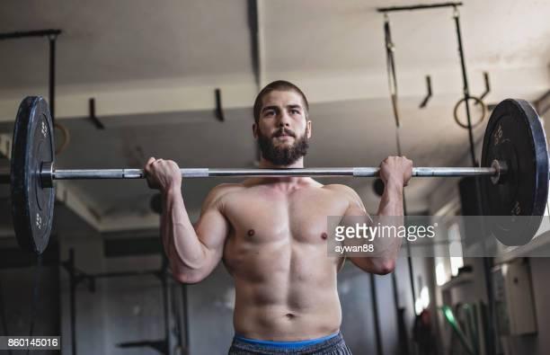 Homme fort exercice avec haltères en gym