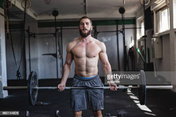 Strong man exercising with barbell