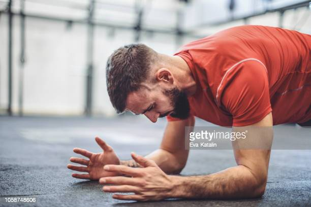 strong man is doing cross training  exercise - plank exercise stock pictures, royalty-free photos & images