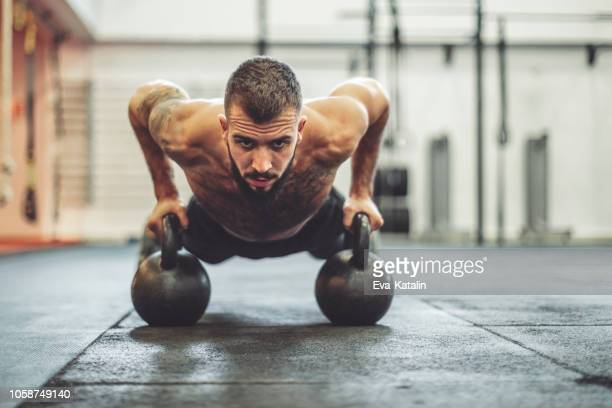 strong man is doing cross training exercise - dumbbell stock pictures, royalty-free photos & images