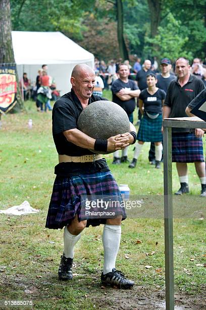 Strong man lifting stone at Highland Games in Trebsen