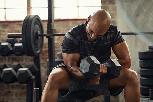 Strong man lifting weight at gym 1149242897