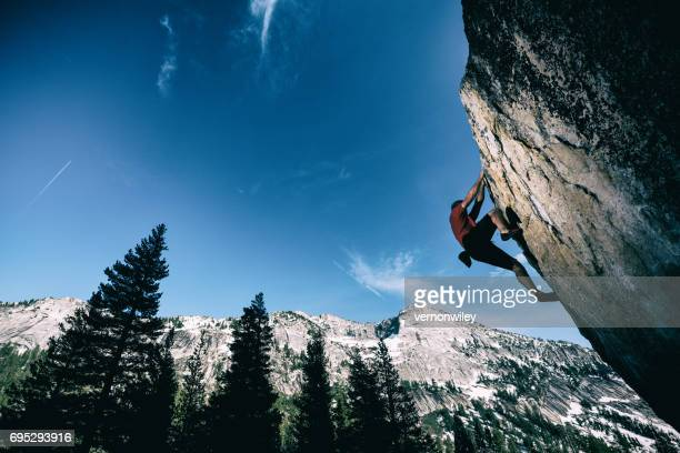 strong man reaching for the top of a boulder - arrampicata su roccia foto e immagini stock