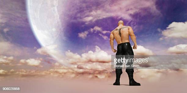 strong man with tattoo on back standing in clouds - giantess stock photos and pictures