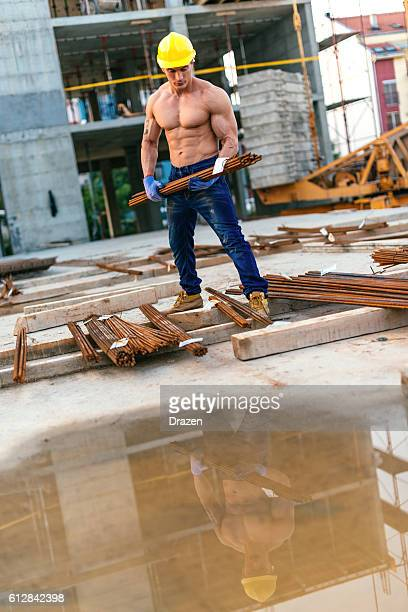 Strong manual worker carrying steel bars and armature
