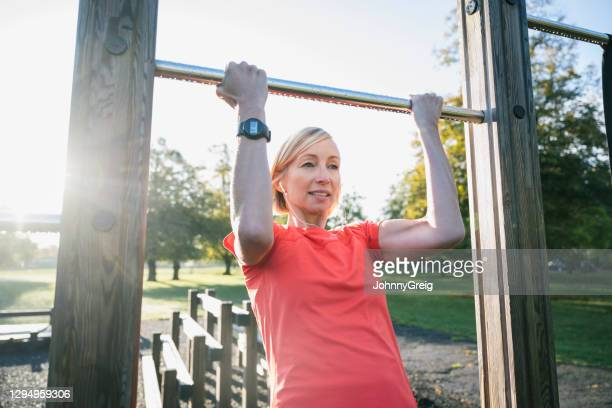 strong mature sportswoman doing chin-ups at public park - clapham common stock pictures, royalty-free photos & images