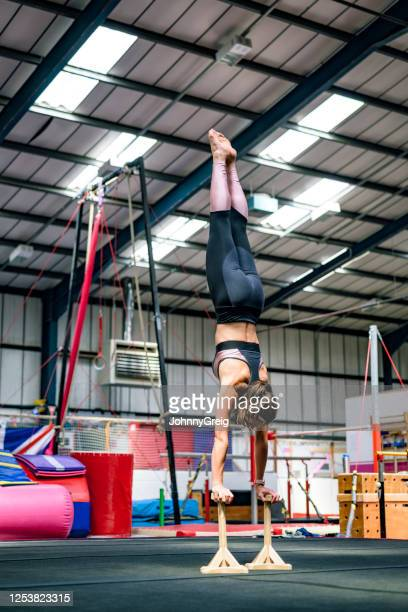 strong mid adult female athlete balancing on handstand canes - floor gymnastics stock pictures, royalty-free photos & images
