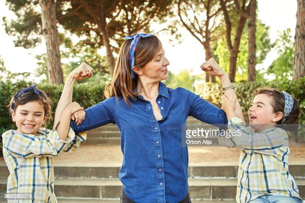 strong mom flexing her arms - girl power - girl power stock photos and pictures