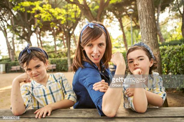 strong mom flexing her arms - girl power - coraggio foto e immagini stock