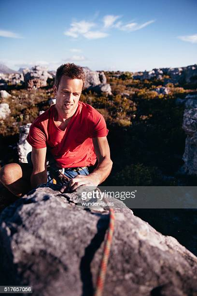 strong rock climbing man reaching peak of mountain conquering challenge - chalk bag stock pictures, royalty-free photos & images