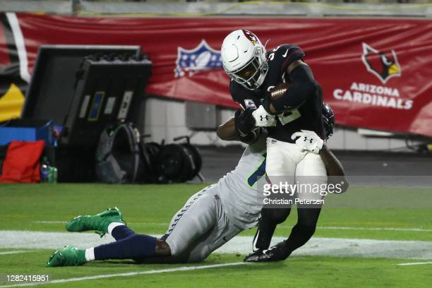 Strong safety Budda Baker of the Arizona Cardinals is tackled by wide receiver DK Metcalf of the Seattle Seahawks after an interception during the...