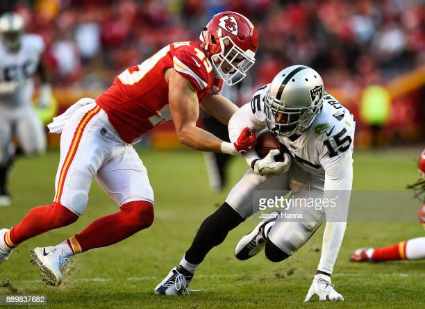 Strong safety Daniel Sorensen of the Kansas City Chiefs attempts to punch out the ball from wide receiver Michael Crabtree of the Oakland Raiders...