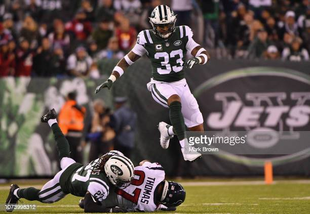 Strong safety Jamal Adams of the New York Jets leaps over teammate cornerback Darryl Roberts and wide receiver Demaryius Thomas of the Houston Texans...