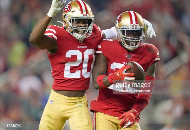 Strong safety Jaquiski Tartt and free safety Jimmie Ward of the San Francisco 49ers celebrate Tartt stripping the ball from wide receiver D.K....