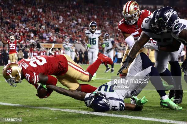 Strong safety Jaquiski Tartt of the San Francisco 49ers strips the ball from wide receiver DK Metcalf of the Seattle Seahawks at the two yard line to...